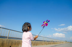 Asian little girl with wind turbine toy in hands Stock Photo