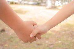 Asian little girls holding hands couple together show Relationsh. Ip between sister and familay at gardren outdoor, Love parents friendship concept Royalty Free Stock Photography