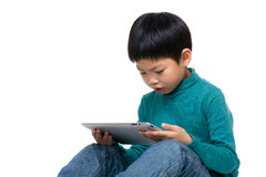 Asian little kid concentrate on reading tablet. Isolated on white Royalty Free Stock Photography