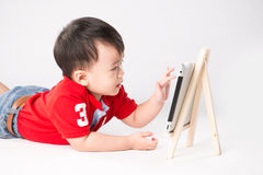 Asian little kid concentrate on reading tablet Stock Images