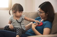 Asian little kid girl examining heartbeat of her mother with ste. Thoscope Royalty Free Stock Photography