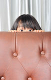 Asian little kid hiding behind a sofa Royalty Free Stock Photo