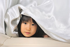 Asian Little kid peeking out from a curtain Stock Images