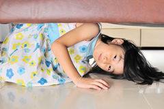 Asian little kid playing and hiding under the sofa Stock Images