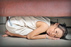 Asian little kid playing and hiding under the sofa Stock Photo
