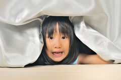 Asian Little kid playing and peeking out from a curtain Royalty Free Stock Image