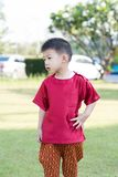 Asian little shot hair boy in the red traditional Thai suit akimbo on his body. An asian little shot hair boy in the red traditional Thai suit akimbo on his Stock Photos