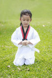 Asian little sitting on green grass field close her eyes with co Royalty Free Stock Image