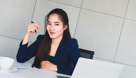 Asian long hair beautiful business woman in navy blue suit smile so happy at her table in office. Have coffee cup, laptop, documen royalty free stock photo