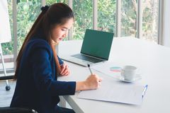 Asian long hair beautiful business woman in navy blue suit working, writing document on the table in office. Tree outside windows. stock photography