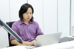 Asian long hair guy focuses and concentrates on his work in front of laptop in the office. stock photo