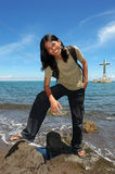 Asian long-haired boy on tropical beach. Asian exotic long-haired boy posing on the rocky beach in front of Sunken Cemetery on the tropical island of Camiguin ( royalty free stock photo