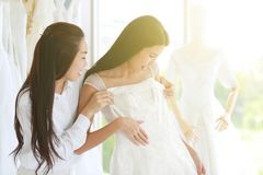 Asian look woman trying on wedding dress and assisting by stylist, happy mood, warm light and soft tone background stock photography