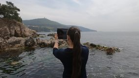 Asian-looking tourist girl takes pictures of Islands, rocks and the sea in Turkey stock video