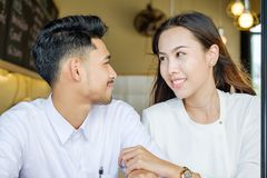 Asian Lover man and woman enjoy with cup of coffee in coffee s royalty free stock image