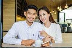 Asian Lover man and woman enjoy with cup of coffee in coffee s royalty free stock images