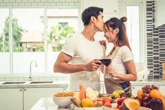 Asian lovers or couples kissing forehead and drinking wine in ki Royalty Free Stock Photo