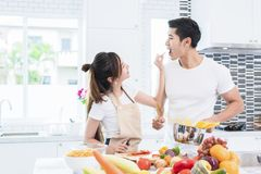 Asian Lovers feeding fruit and food to each other, Couple and Family concept. Honeymoon and Holidays theme. Indoor interior.  stock photography