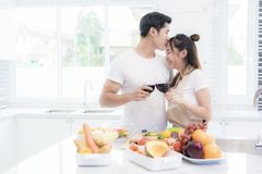 Asian lovers in kitchen, Man give forehead kiss to woman while clink wine glasses to each other. Family and Couple concept. stock photo