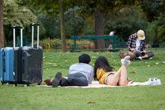 Asian loving couple of tourists with suitcases lies on the green grass in the park. The Champ de Mars in Paris royalty free stock image