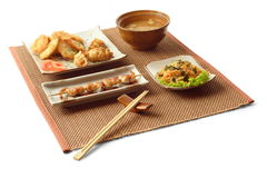 Asian lunch 1. Asian lunch with salad, gedze, tempura, miso soup, kani sarada, yakitori tori and chopsticks on the matting over white background Royalty Free Stock Image