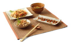 Asian lunch 2. Asian lunch with meat salad, soup with mushrooms, udon with pork and vegetables, yakitori and chopsticks on the matting over white background Royalty Free Stock Images