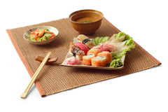 Asian lunch 4. Asian lunch with rolls, sashimi, isumi-dai, maguro, unagi, tomato, miso soup, salad and chopsticks on the matting over white background Royalty Free Stock Images