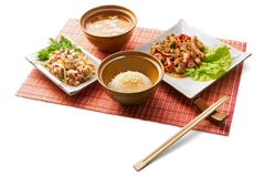 Asian lunch 8. Asian lunch with rice, miso soup, boiled meat, shrimp tempura and chopsticks on the matting over white background Royalty Free Stock Photo