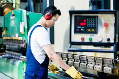 Asian machine operator in production plant stock images