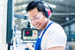 Asian machine operator in production plant Royalty Free Stock Photos