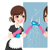 Asian Maid Cleaning Mirror. Beautiful Asian woman in maid dress working cleaning mirror using squeegee to wash mirror Royalty Free Stock Photography