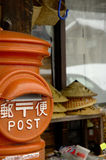 Asian Mailbox. Mailbox in rural Japan.  It is bright orange with POST written in both English and Japanese characters.  There are hats and baskets for sale in Stock Photos