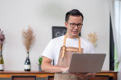 Asian male Barista cafe owner using laptop checking stock business inside coffee shop, food and drink business start up.  royalty free stock image
