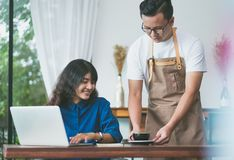 Asian male barista holding coffee cup served to customer at tabl. E,Cafe restaurant service concept,Owner small business concept Royalty Free Stock Photo