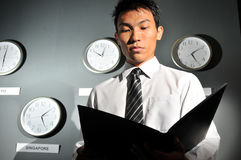 Asian Male Boss scrutinizing office work Royalty Free Stock Photos