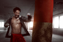 Asian male boxer practicing with a punching bag Stock Photos