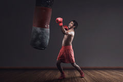 Asian male boxer practicing with a punching bag Royalty Free Stock Photo