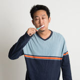 Asian male brushing teeth Royalty Free Stock Photos