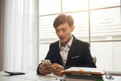 Asian male businessman is using phone stock images