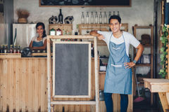 Asian male cafe owner with blank board. Portrait of confident young asian male cafe owner standing with blank board Stock Photos