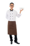 Asian male chef. Full body Asian chef holding an empty plate ready for food, standing isolated on white background royalty free stock photo