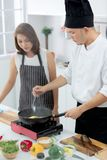 Asian male chef demonstrating how to cook for beautiful student royalty free stock image