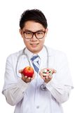 Asian male doctor with apple and medicine stock images