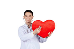 Asian male doctor auscultation a red heart with a stethoscope,. Isolated on white stock image