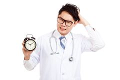 Asian male doctor in bad mood with a clock. Isolated on white background stock images