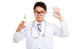 Asian male doctor hold syringe show OK sign Royalty Free Stock Photography