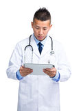 Asian male doctor look at digital tablet Stock Images