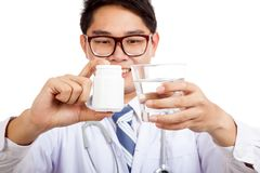 Asian male doctor with pharmacy bottle and water Royalty Free Stock Photography