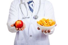 Asian male doctor with red apple and potato chips Royalty Free Stock Photography
