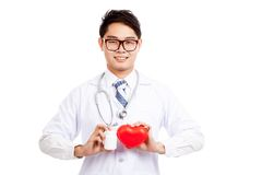 Asian male doctor with red heart and pill bottle Stock Photo